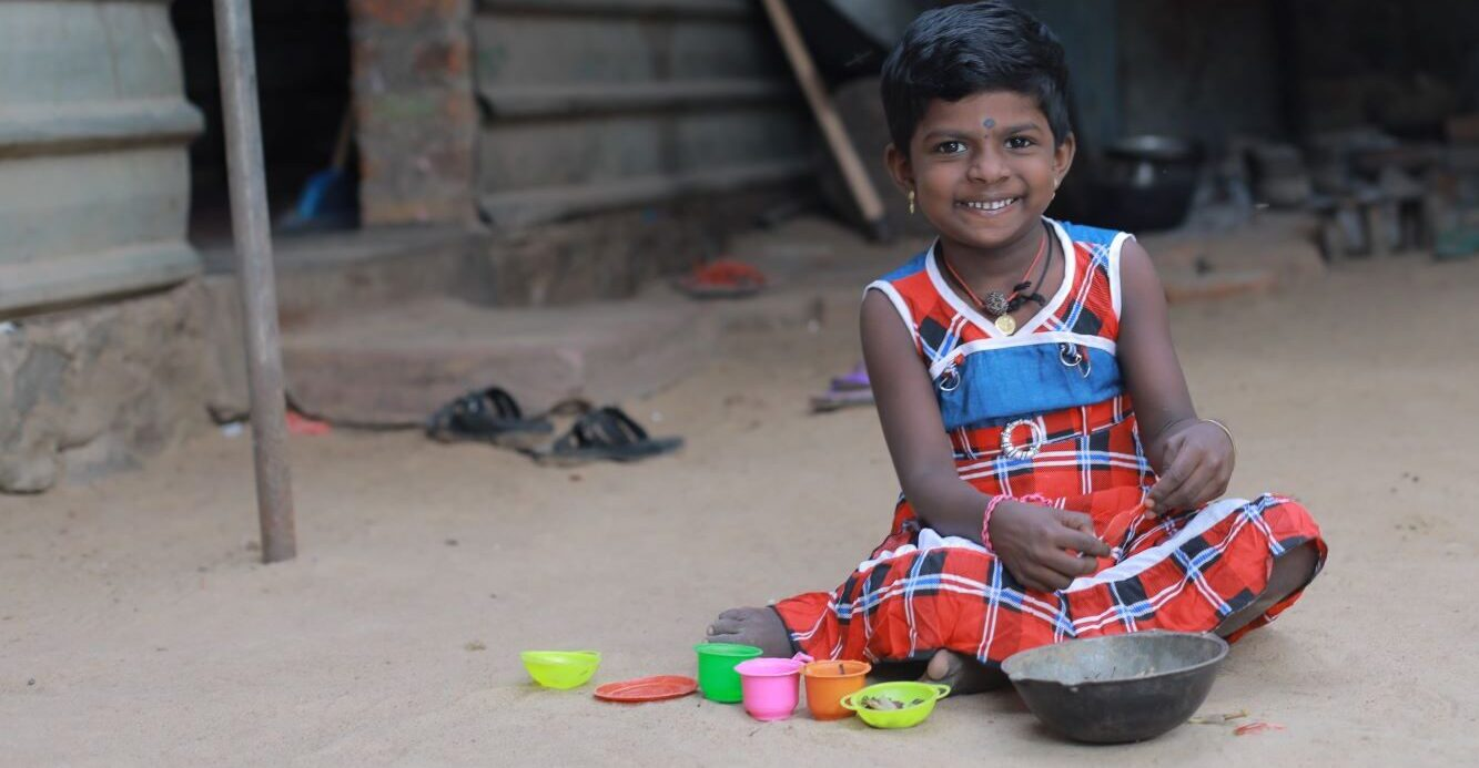 Sri Lankan girl playing with cooking toys